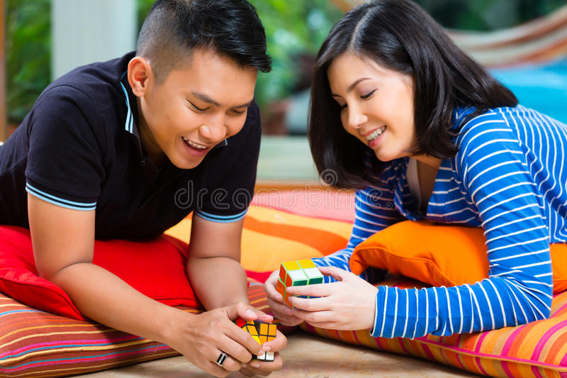 Download Asian Couple At Home Playing With Magic Cube Editorial Photo - Image: 31285516