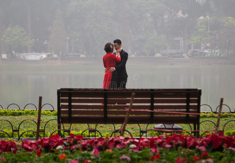 Asian couple hugging and kissing in a beautiful outdoor view. Hanoi, Vietnam - Jan 16, 2016: Asian couple hugging and kissing in a beautiful outdoor view with stock image
