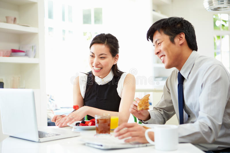 Asian Couple Looking at Laptop Over Breakfast stock images