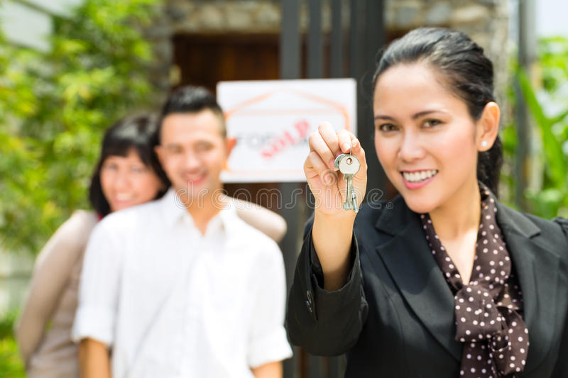 Asian couple looking for real estate. Real estate market - young Indonesian couple looking for real estate apartment or house to rent or buy, the realtor holding royalty free stock images