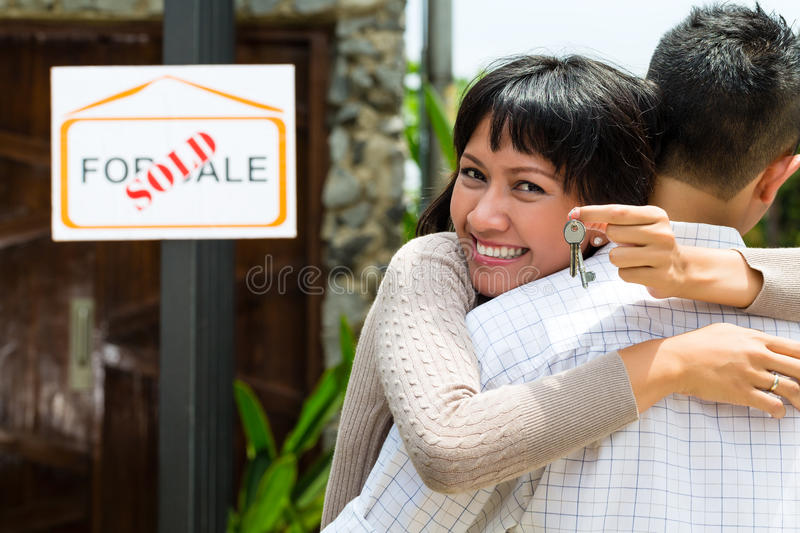 Asian couple looking for real estate. Real estate market - young Indonesian couple looking for real estate apartment or house to rent or buy, the women holding royalty free stock image