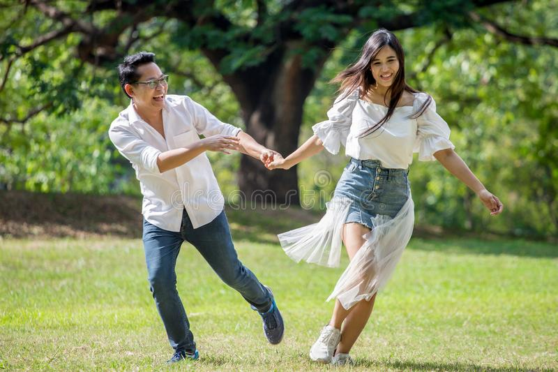 asian couple in love running in park  having happiness and joy stock images