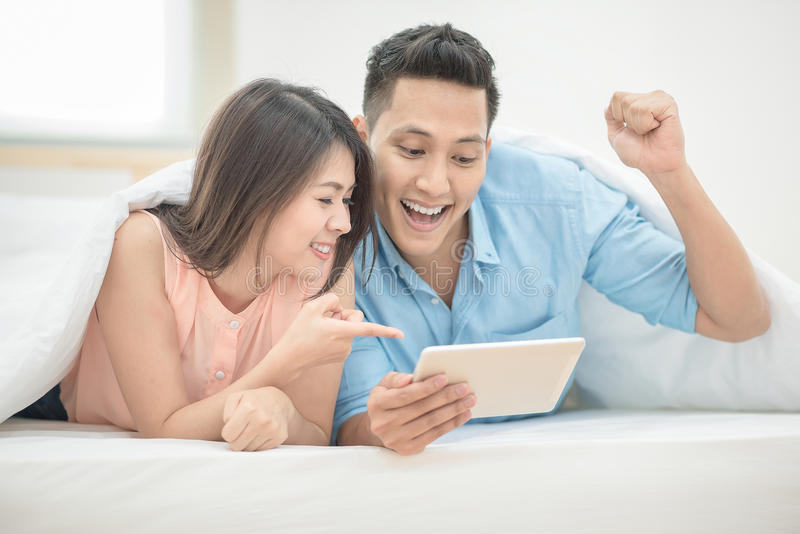 Asian couple lovers enjoy cheer up online esport. On smart tablet on holiday vacation in bedroom stock photos