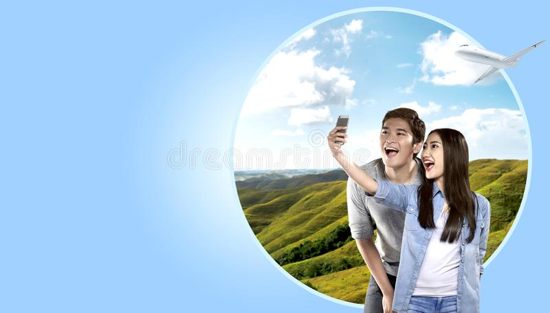 Asian couple making selfie on mobile phone camera with green hills background stock photos