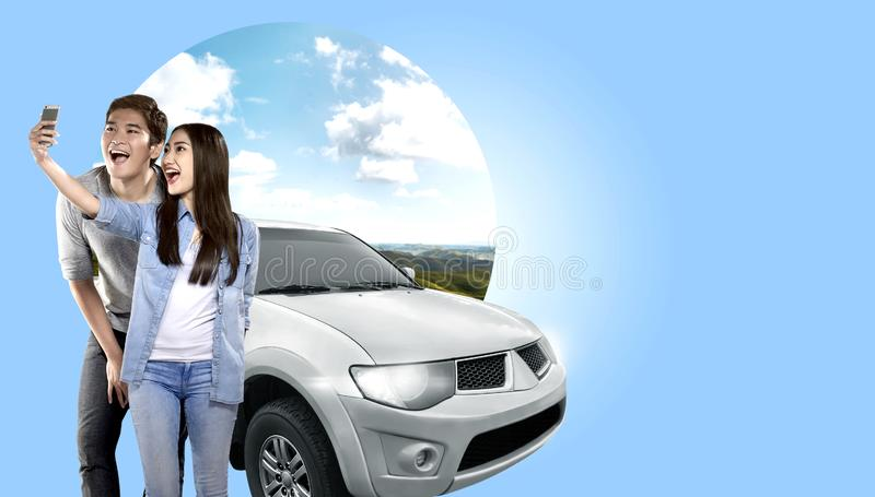 Asian couple making selfie on mobile phone camera posing beside automobile with green hills background stock photography