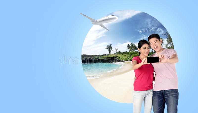 Asian couple making selfie on mobile phone camera with sandy beach background royalty free stock images