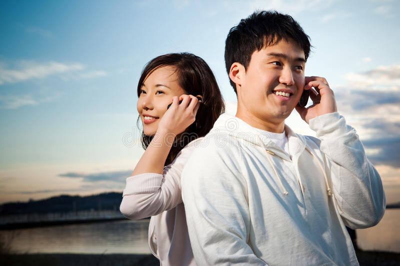 Asian couple on the phone royalty free stock photos