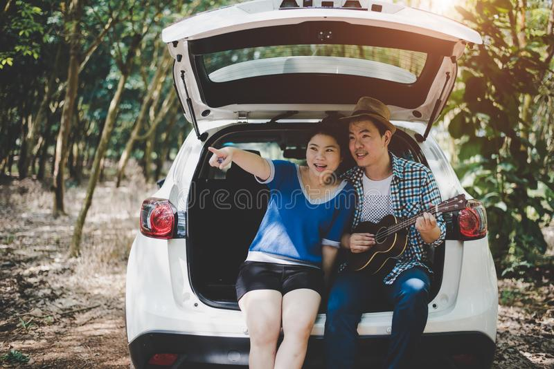 Asian couple pointing and traveling into forest by car, Musician lover. Adventure and outdoors concept. Nature and Lifestyle theme. Road trip theme, behind stock photo