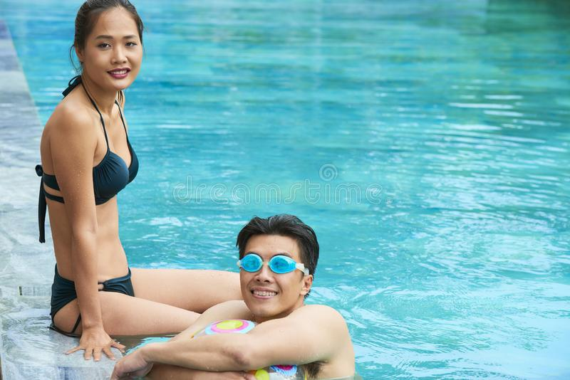 Asian couple resting in swimming pool royalty free stock photography