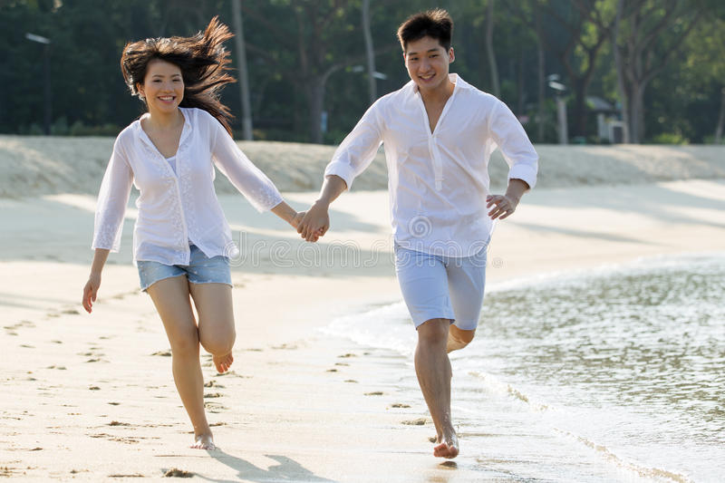 Download Asian Couple Running The Beach. Stock Image - Image: 24845695