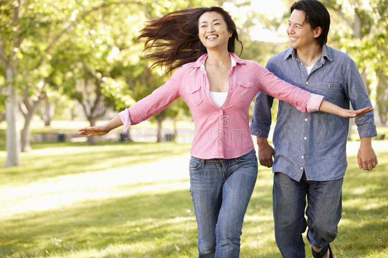Asian couple running through in park royalty free stock photography