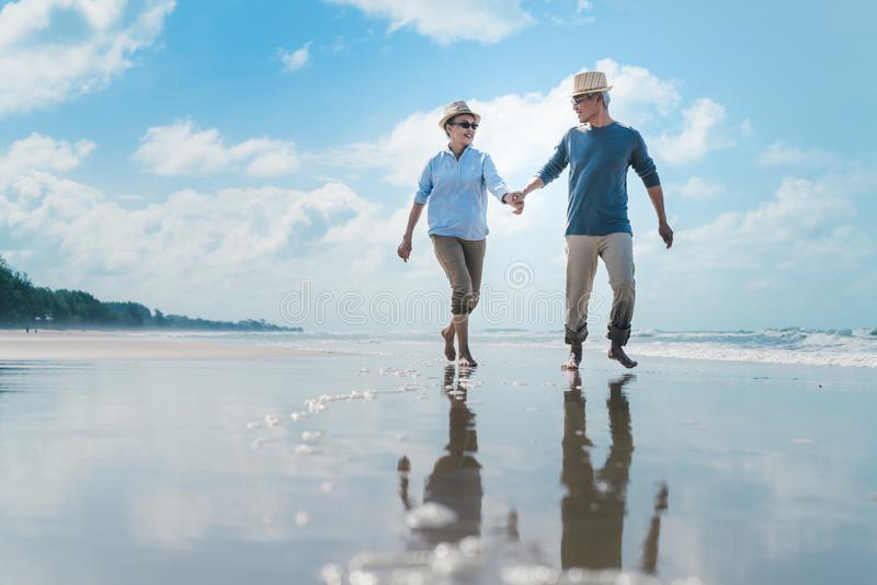 Asian couple senior elder retire resting relax walking running at sunset beach honeymoon stock photos