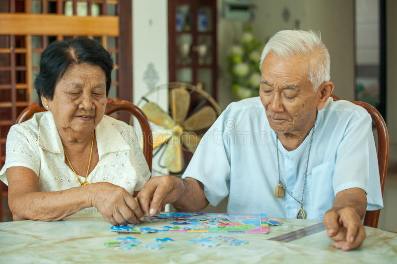 Asian couple senior playing with a jigsaw puzzle stock images