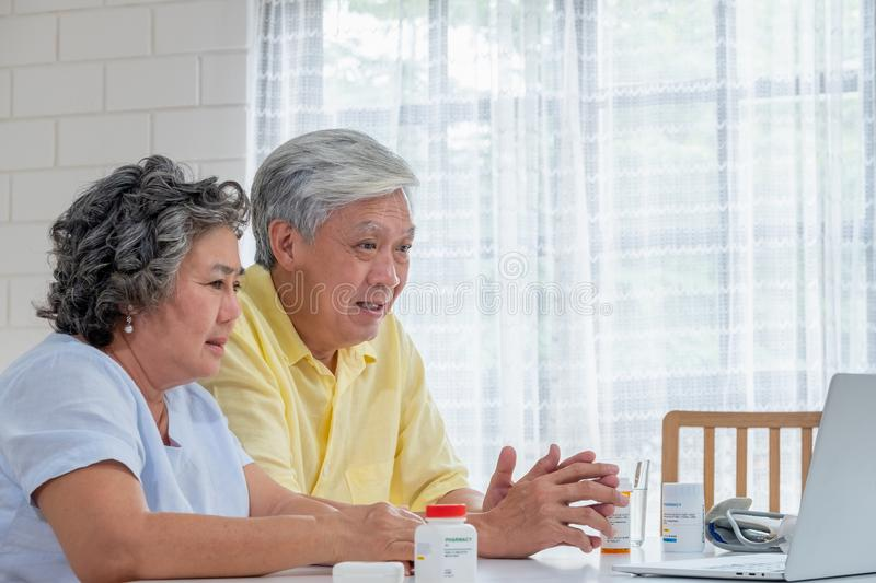 Asian couple seniors use laptop video conference with doctor about illness and prescription pill in living room at home.Healthy stock photography