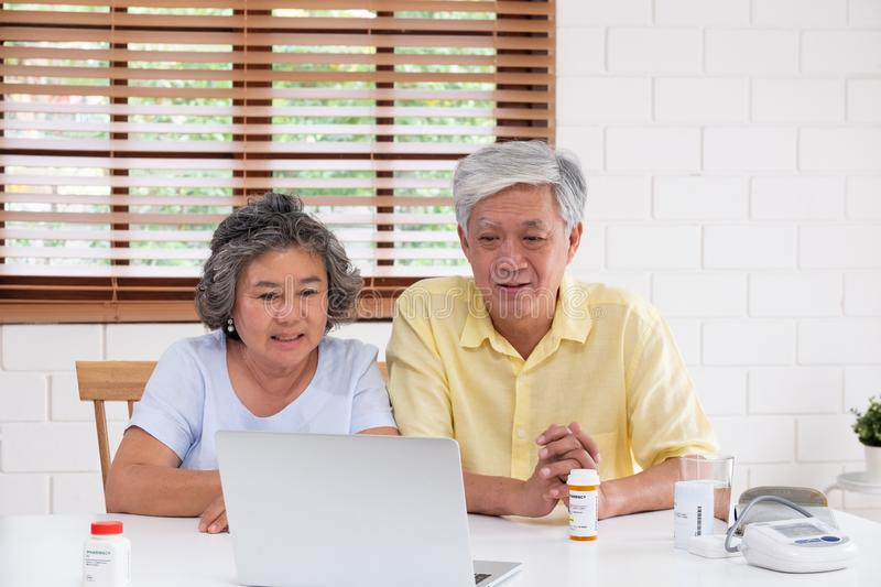 Asian couple seniors use laptop video conference with doctor about illness and prescription pill in living room at home.Healthy. Lifestyle.aging at home concept stock images