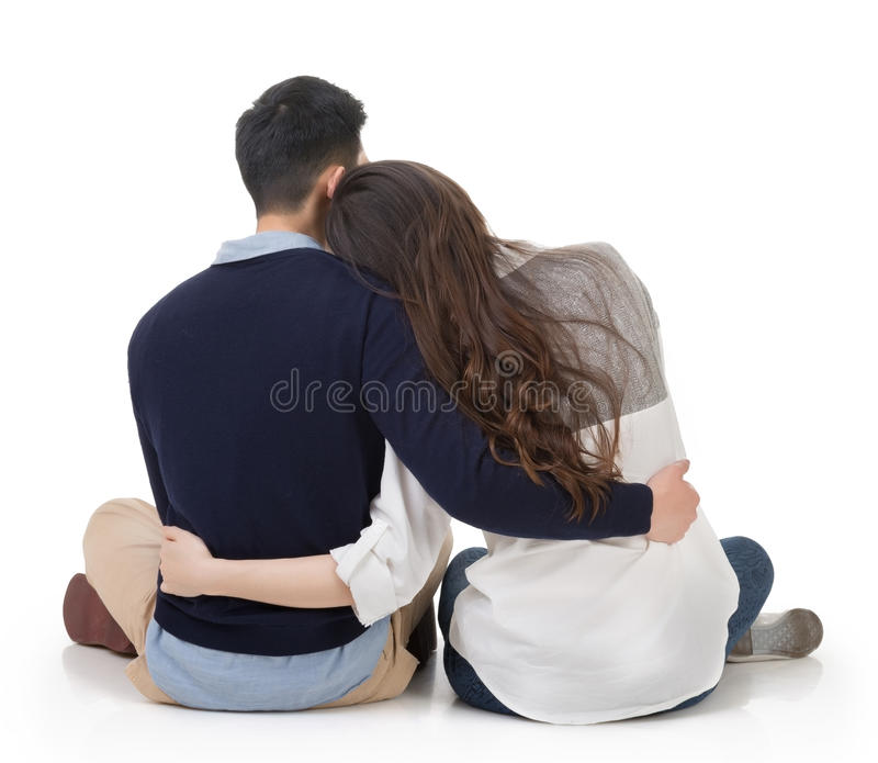Asian couple sit on ground. And hug each other, rear view on white background stock photography
