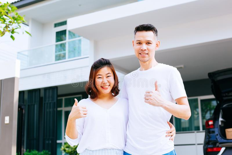 Asian couple standing in front of their new house and giving thumbs up royalty free stock images