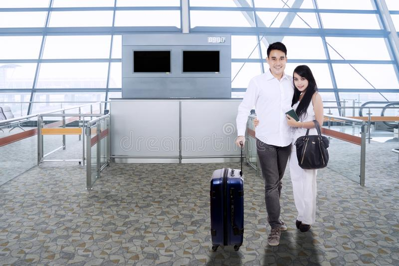 Asian couple with suitcase smiling in airport terminal royalty free stock photography