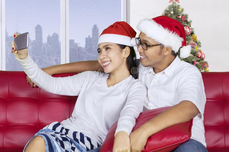 Asian couple taking photo in the apartment. Asian couple wearing Santa Claus hat while taking a selfie photo with a smartphone in the apartment royalty free stock image