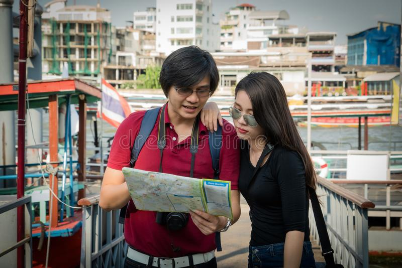 Asian couple tourist backpackers looking for direction stock photo