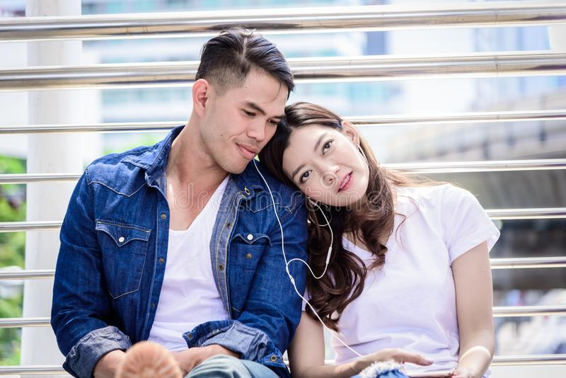 Asian couple tourist have music listening together. stock photo