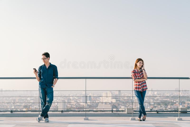 Asian couple using telephone call and smartphone together on building roof. Mobile cellphone device or information technology. Young Asian couple using telephone stock photo