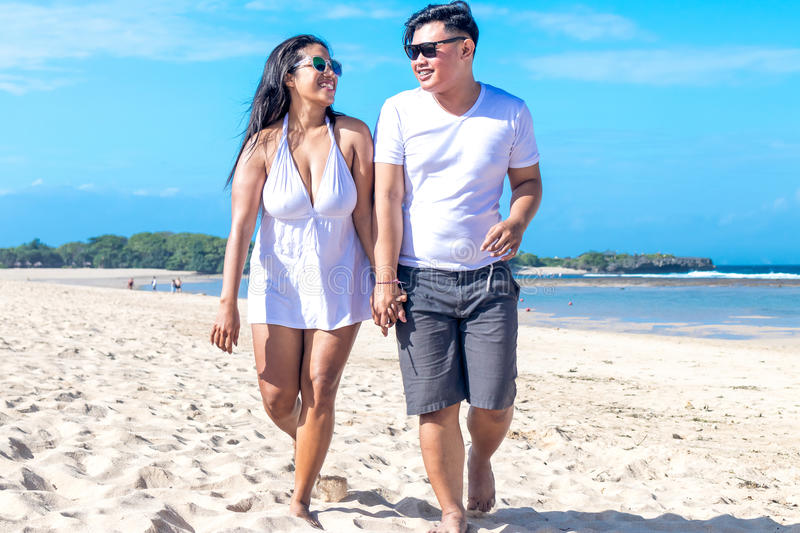 Asian couple walking on the beach of tropical Bali island, Indonesia. stock image
