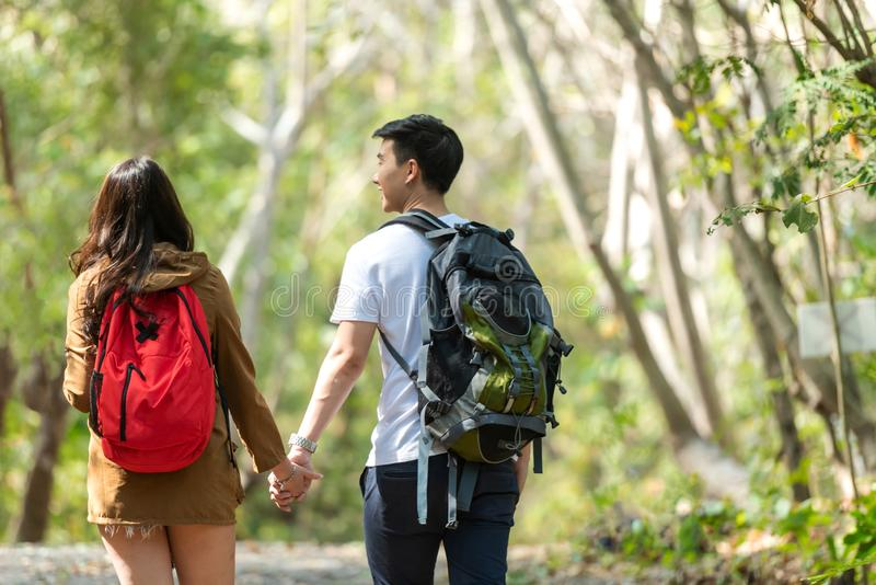 Asian Couple walking for explore and find directions in the camping jungle nature and adventure. Tourism man and woman travel for. Asian Couple walking for stock images
