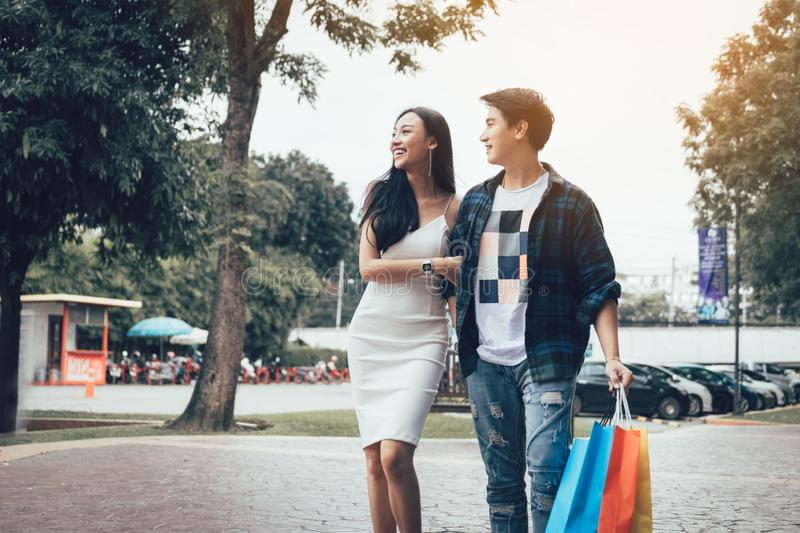 Asian couple walking at shopping mall looking product inside mirror retail.  royalty free stock photos