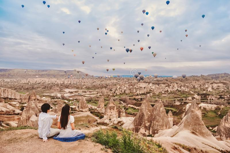Asian couple watching colorful hot air balloons flying over the valley at Cappadocia, Turkey This Romantic time of love.  stock images