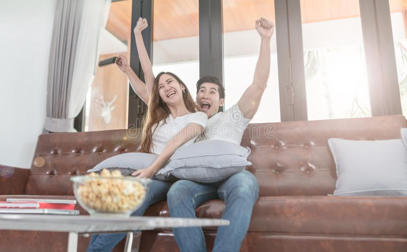 Asian couple watching TV sitting on a couch at home.  stock photo