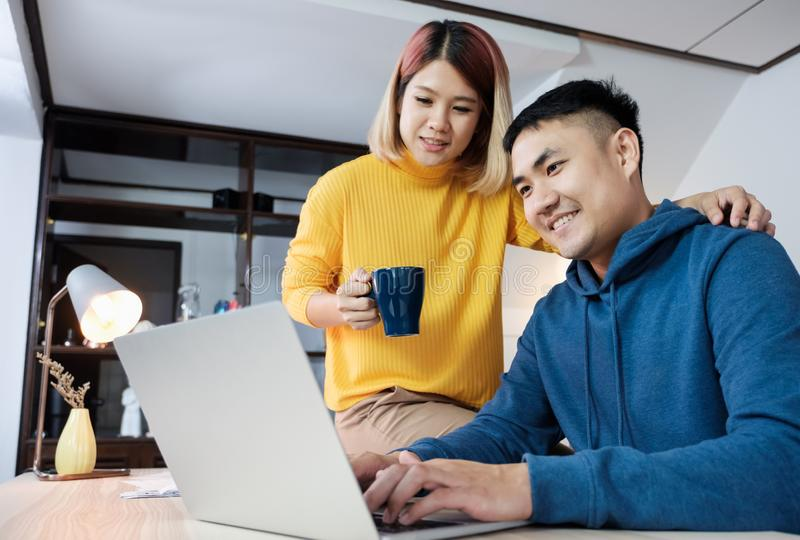 Asian couple watching video live on laptop at table at home.lover spending time together. Asian couple watching video live on laptop at table at home.lover royalty free stock photography