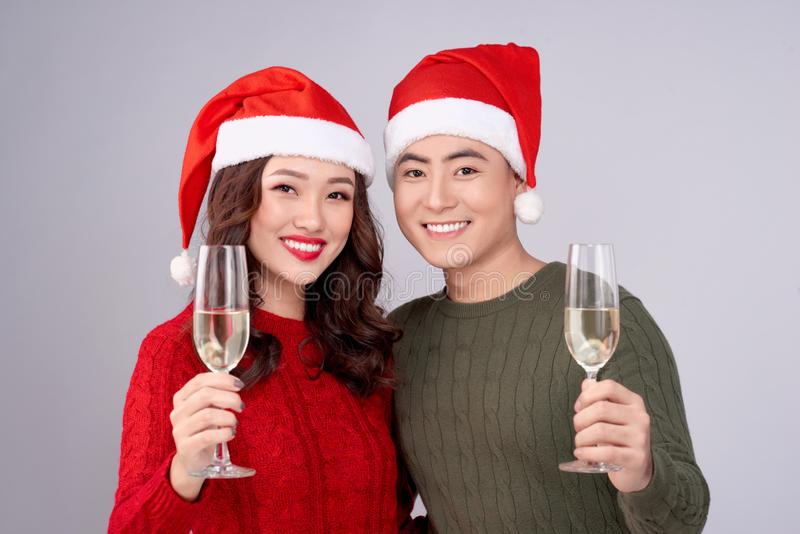 Asian couple wearing christmas hat and dress holding champagne glass stock image