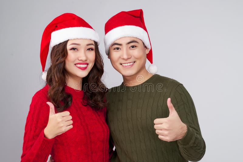 Asian couple wearing christmas hat gesture hands. Asian couple wearing christmas hat gesture hands stock image