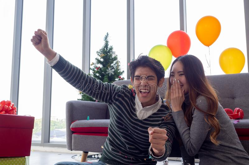 Asian couple whispered a secret and raised his hand to express happiness with success or good news or getting pregnant on New Year. `s Day stock photography