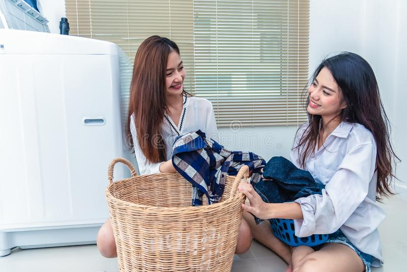 Asian couple women doing housework and chores in front of washing machine and loading clothes in laundry room together. People royalty free stock photo