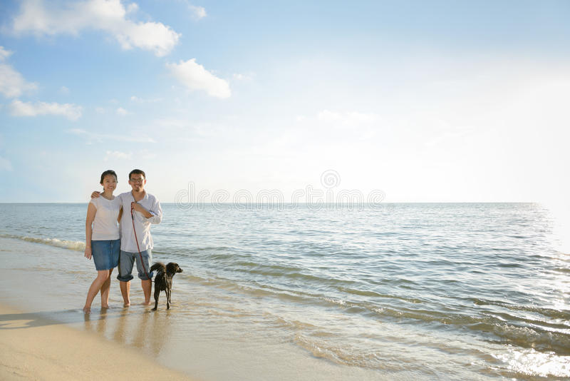 Couples with dog at beach royalty free stock photo