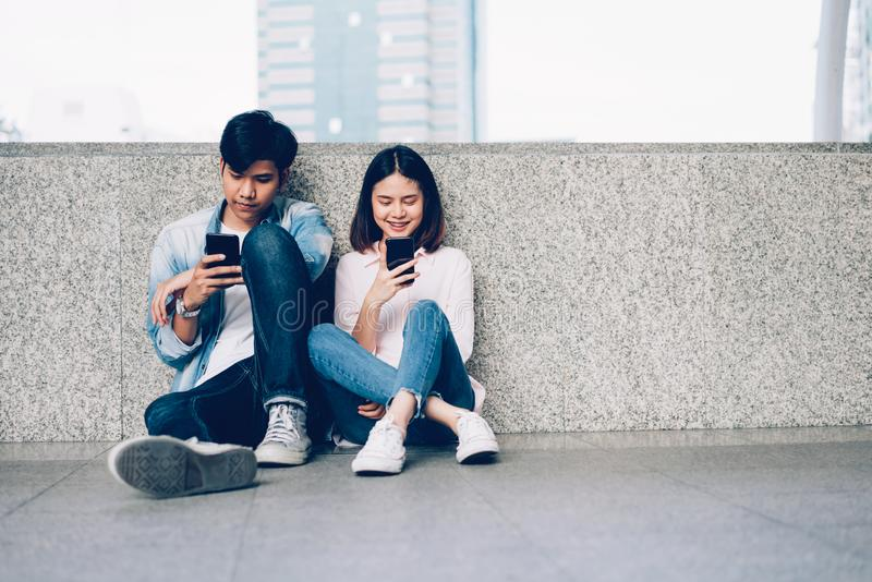 Asian couples of happy smiling sitting using smartphone in covered walkway. The concept of using the phone is essential in everyday life stock photos