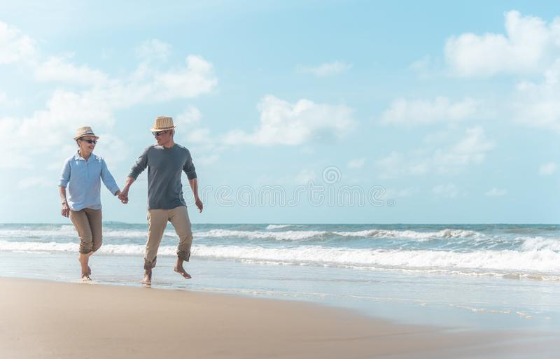 Asian couples, seniors are walking and resting on the beach in the morning stock image