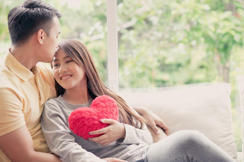 Asian Couples Sitting on the sofa In which women Holding a red heart And smiling happily. Concept of expressions of love and warmt royalty free stock images