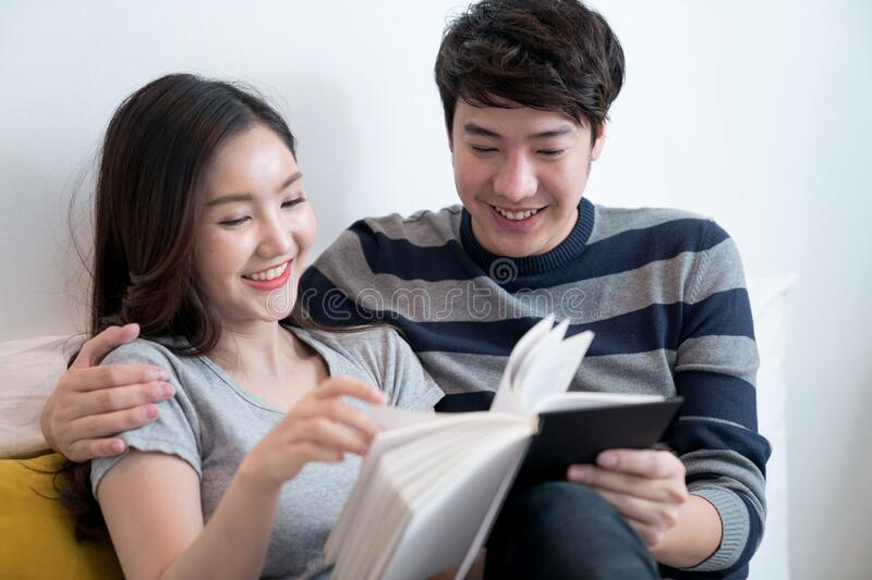 Asian couples spend time together at home, They read books together. The concept of living together stock image