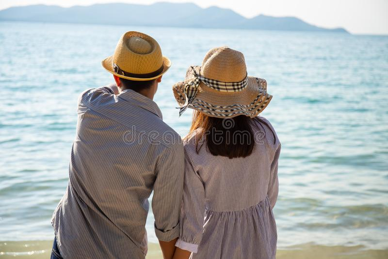 Asian couples stand hand in hand at the sea. Side at promenade on a sunny day stock photo