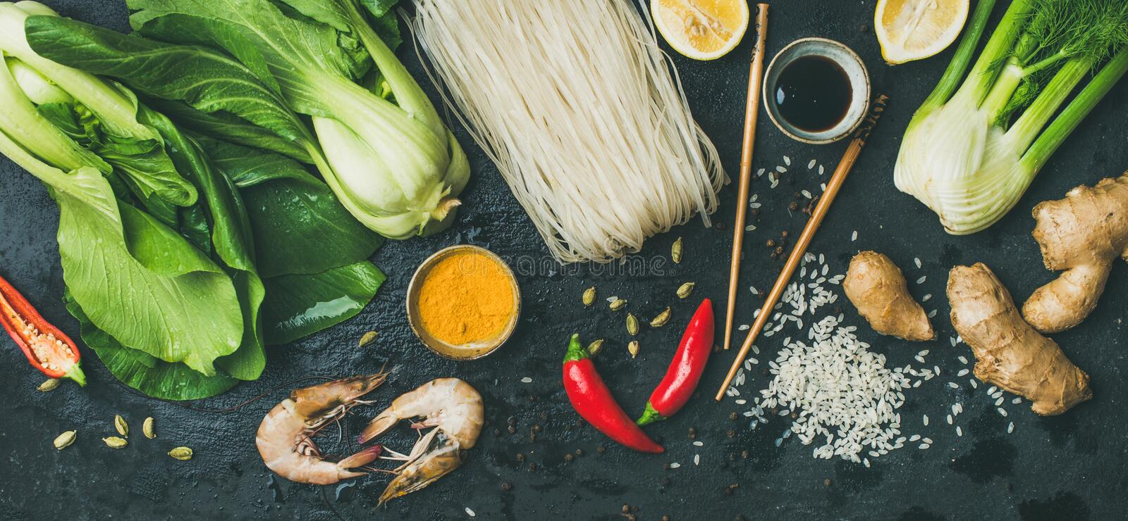 Asian cuisine ingredients over dark slate stone background, top view. Vegetables, spices, shrimp, rice, sauces for cooking vietnamese, thai or chinese food royalty free stock photos