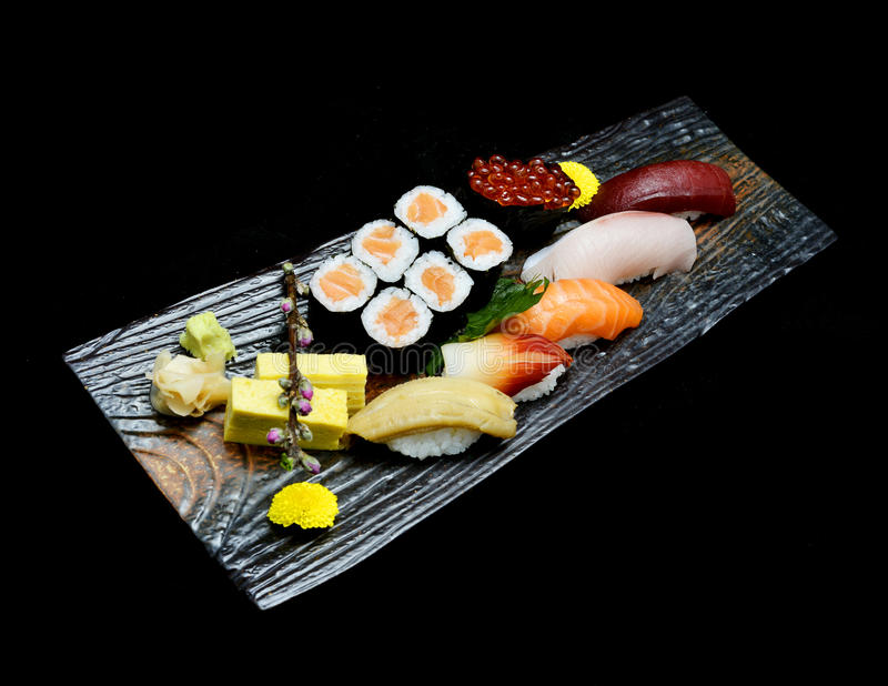 Asian cuisine or Japanese food. Sushi medium set on wooden plate. With black isolated background stock photos