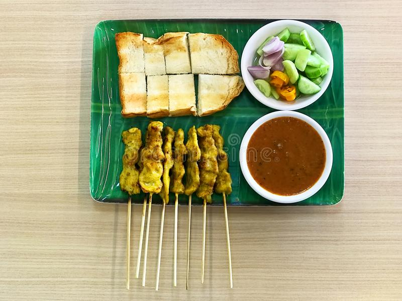 Asian Cuisine, Pig Satay or Moo Satay with toast on green dish and wood table. stock photo