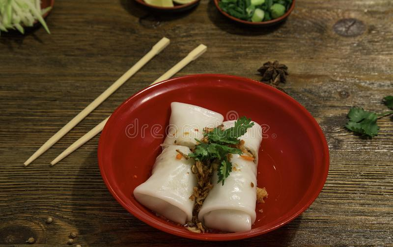 Asian cuisine rice paper rolls with vegetables and prawns on red plate and chopsticks.  stock photography