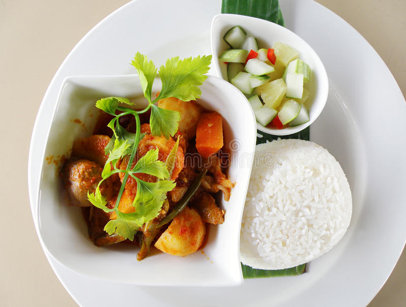 Asian curry dish with rice ethnic food. A delicious meal of spicy chicken curry served with white rice and sour pickles of cucumber, pineapple and chilli. Served stock photos