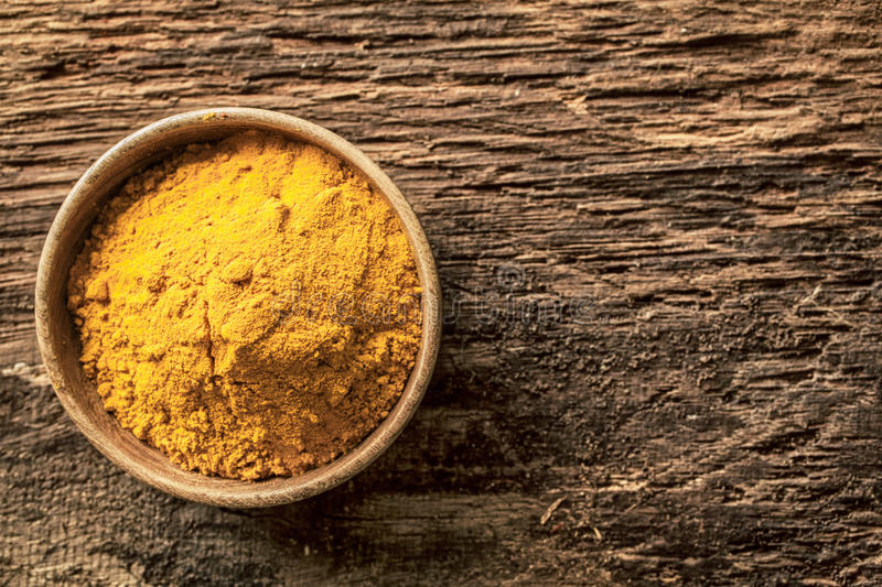 Asian curry powder. Made from a blend of spices with a masala or turmeric base in a small bowl on a grunge textured wooden surface, overhead view with copyspace stock images
