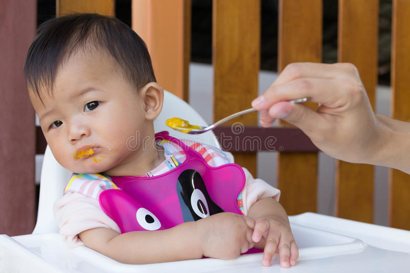 Asian cute baby boring eat food. Asian cute baby boring eat food, Mother feeding solid food for young kid eight month royalty free stock photo