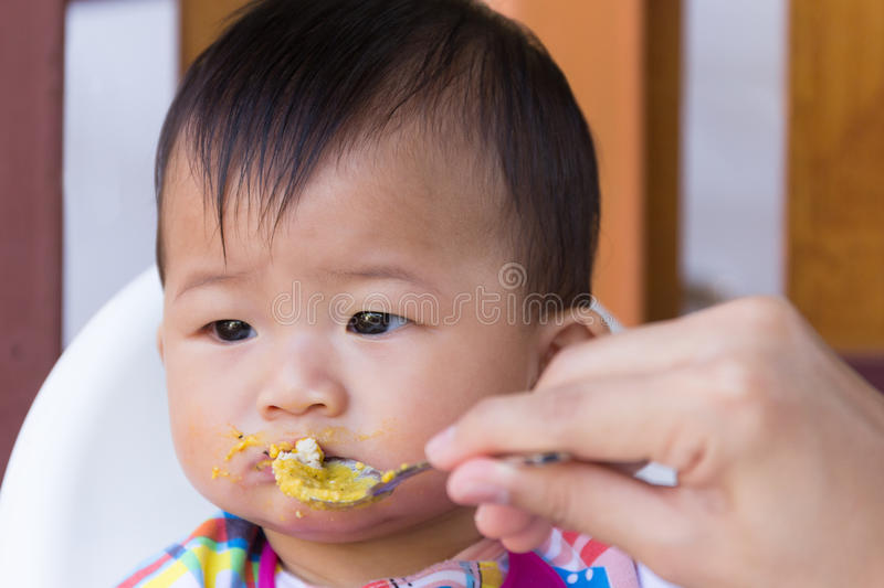 Asian cute baby boring eat food. Asian cute baby boring eat food, Mother feeding solid food for young kid eight month royalty free stock photos